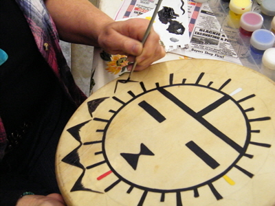 Kate Silberberg painting Hopi Sunface drum.
